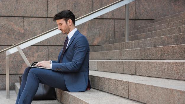Geschäftsmann, der laptop auf schritten verwendet Kostenlose Fotos