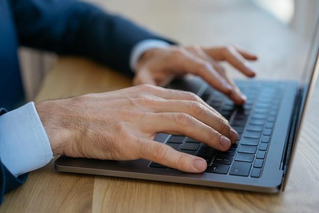 Geschäftsmann, der laptop benutzt, tippt, informationen sucht, im büro sitzt. freiberufler, der von zu hause aus arbeitet Premium Fotos