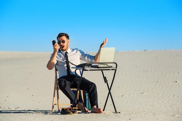 Geschäftsmann, der laptop in einer wüste benutzt Kostenlose Fotos