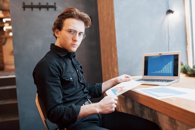 Geschäftsmann, der laptop mit tablette und stift auf holztisch im kaffeehaus mit einer tasse kaffee verwendet. ein unternehmer, der sein unternehmen als freiberufler aus der ferne leitet. Kostenlose Fotos