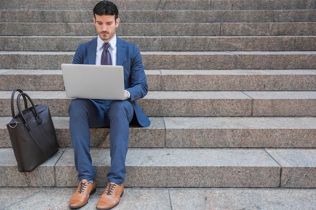 Geschäftsmann, der laptop nahe tasche verwendet Kostenlose Fotos