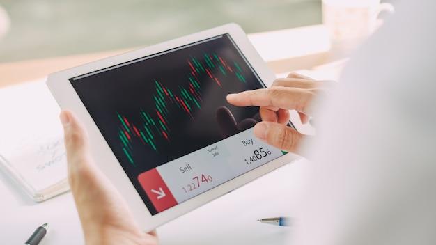 Geschäftsmann, der markthandel und austausch mit dokumentengraphiken auf intelligentem gerät analysiert. Premium Fotos