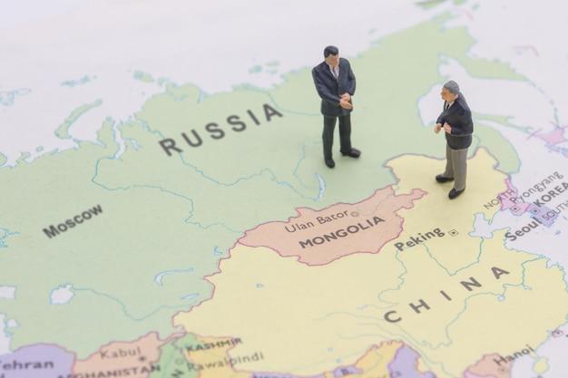 Geschäftsmann der miniatur zwei shakehand auf porzellan- und russischer karte Premium Fotos
