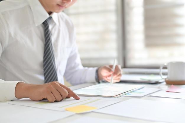 Geschäftsmann, der mit analysedaten bezüglich der digitalen tablette arbeitet. Premium Fotos