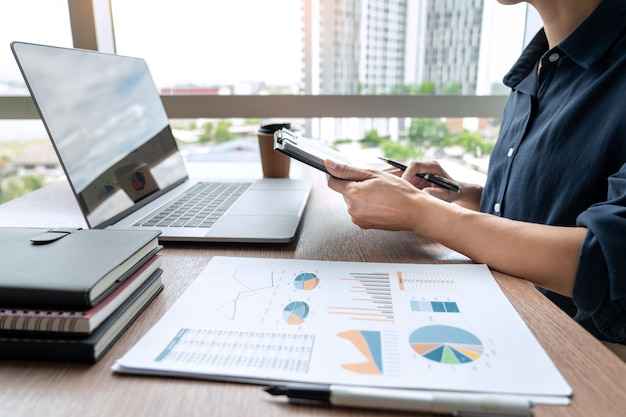 Geschäftsmann, der mit diagrammdaten im laptop und in den dokumenten auf seinem schreibtisch im büro arbeitet. Premium Fotos