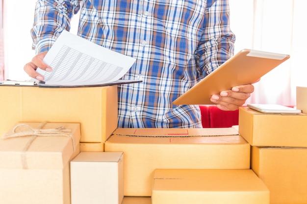 Geschäftsmann, der mit handy arbeitet und zu hause büro des braunen paketkastens verpackt. händeverkäufer bereiten das produkt vor, das bereit ist, zum kunden zu liefern. online-verkauf, e-commerce starten sie versand-konzept. Premium Fotos