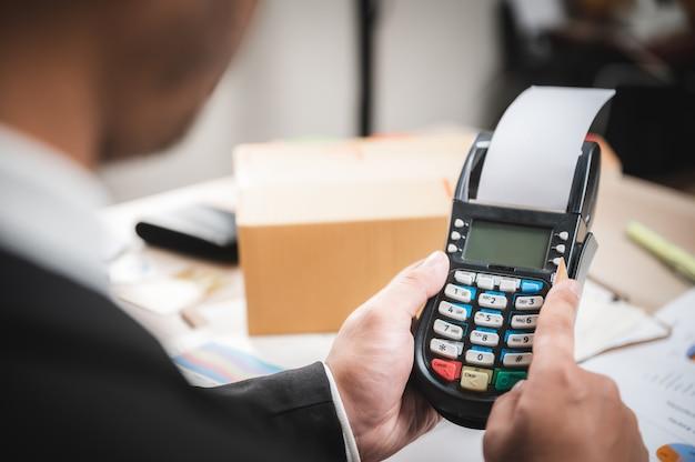 Geschäftsmann, der mit kreditkarte mit einem kreditkartenlesegerät, e-banking und online-geschäftsmarketingkonzept zahlt Premium Fotos