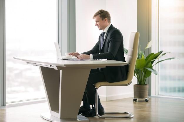 Geschäftsmann, der mit laptop am moderm schreibtisch arbeitet Kostenlose Fotos