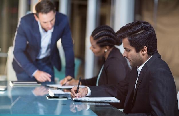 Geschäftsmann, der mit mitarbeitern in einer besprechung im konferenzraum interagiert Premium Fotos