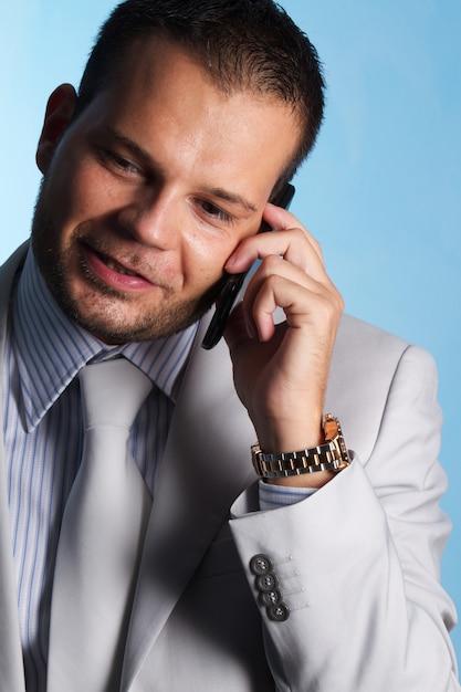Geschäftsmann, der mit mobile im büro spricht Premium Fotos