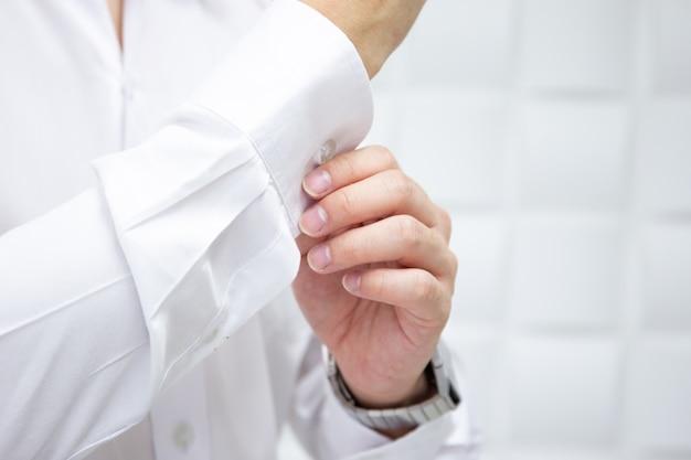 Geschäftsmann, der oben seinen hemdabschluß justiert. Premium Fotos