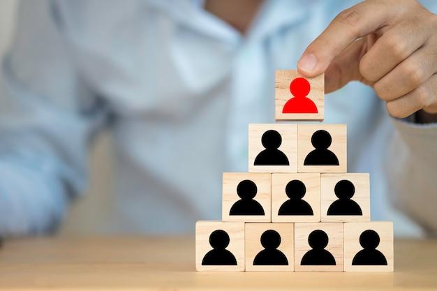 Geschäftsmann, der rote illustration setzt, die das rote menschliche symbol des bildschirms oben auf das schwarze menschliche symbol druckte. leitschiff- und teamwork-konzept. Premium Fotos