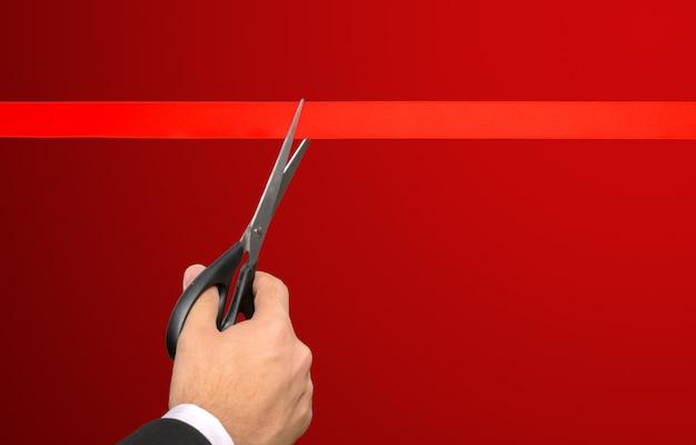 Geschäftsmann, der rotes band mit schere schneidet Premium Fotos
