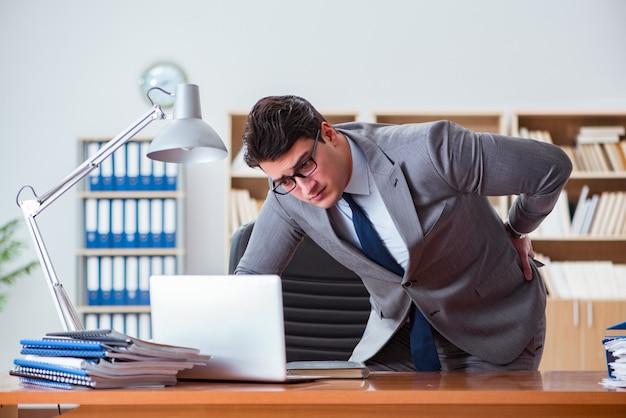 Geschäftsmann, der schmerz im büro glaubt Premium Fotos