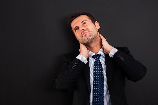 Geschäftsmann, der schmerzen im nacken hat Kostenlose Fotos
