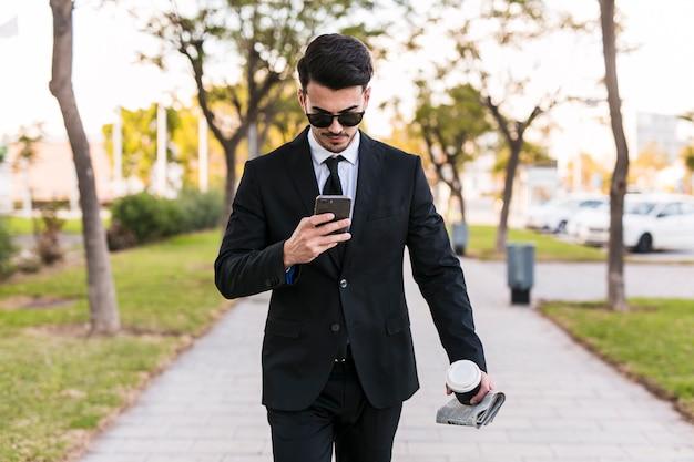 Geschäftsmann, der sein telefon auf den park betrachtet Kostenlose Fotos