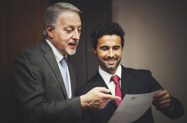 Geschäftsmann, der seinem kollegen ein dokument zeigt Premium Fotos