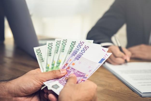 Geschäftsmann, der seinem partner geld, eurowährung, gibt Premium Fotos