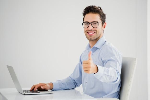 Geschäftsmann, der sich daumen bei der anwendung des laptops zeigt Premium Fotos