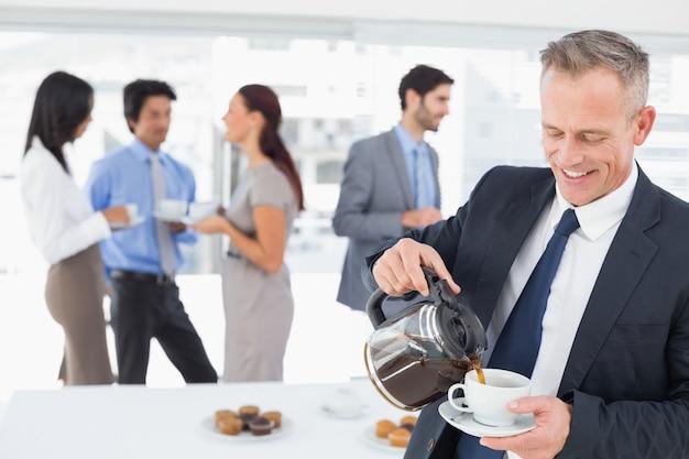 Geschäftsmann, der sich etwas kaffee gießt Premium Fotos