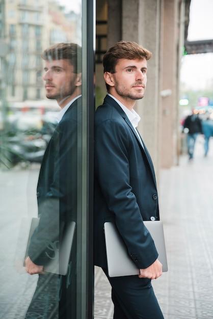 Geschäftsmann, der sich sicher auf einer dunklen glaswand in der hand hält digitale tablette lehnt Kostenlose Fotos