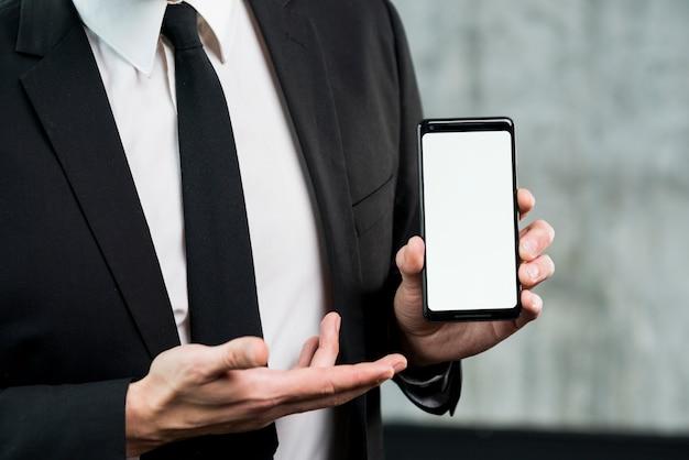 Geschäftsmann, der smartphone mit leerem bildschirm zeigt Kostenlose Fotos