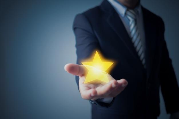 Geschäftsmann, der sternbewertung oder ziel auf dunkelblauem zeigt Premium Fotos