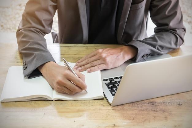 Geschäftsmann, der stift und laptop dann auf notizbuch am arbeitsplatz schreibt. Premium Fotos