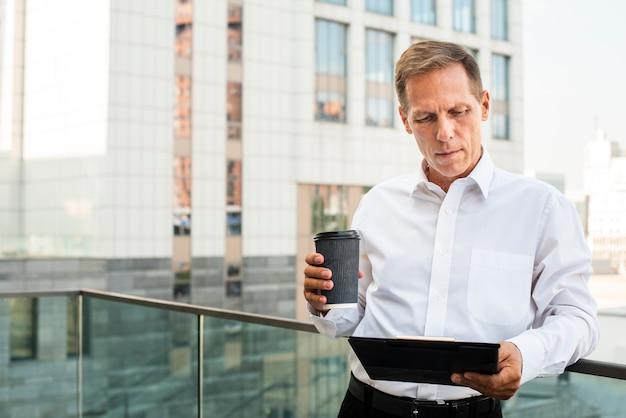 Geschäftsmann, der tablette beim halten des kaffees betrachtet Kostenlose Fotos