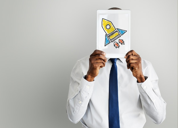 Geschäftsmann, der tablette mit raketenraumschiffikone hält Premium Fotos