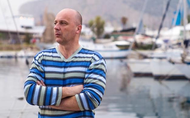 Geschäftsmann, der teure segelboote und yachten in einer küstenstadt bereitsteht Premium Fotos