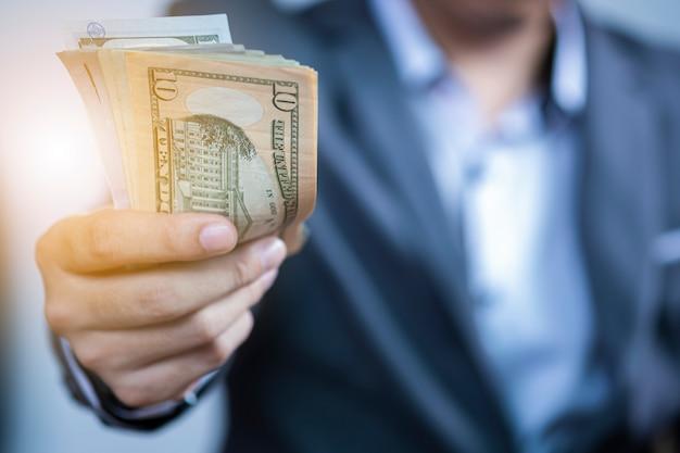 Geschäftsmann, der usd-banknote für zahlung hält. Premium Fotos