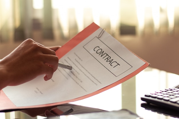 Geschäftsmann, der wichtige dokumente liest, bevor dokumente im büro unterzeichnet werden. Premium Fotos
