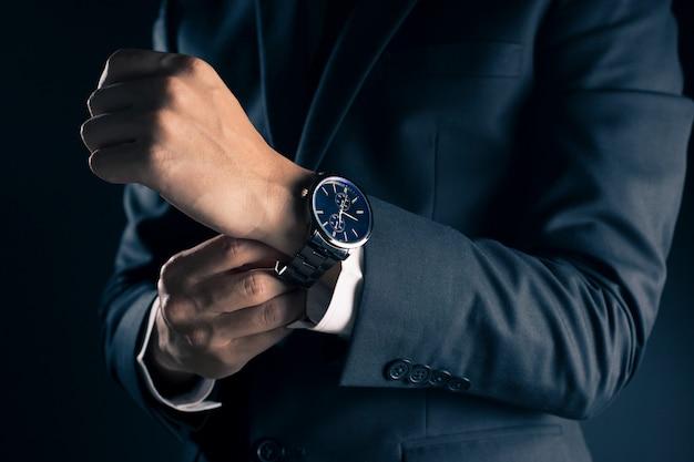 Geschäftsmann, der zeit von der uhr überprüft Premium Fotos