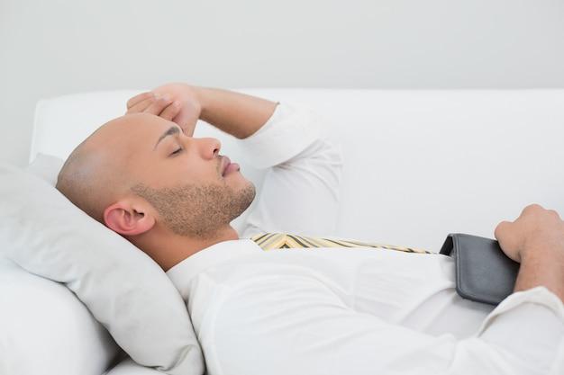 Geschäftsmann, der zu hause auf sofa mit digitaler tablette schläft Premium Fotos