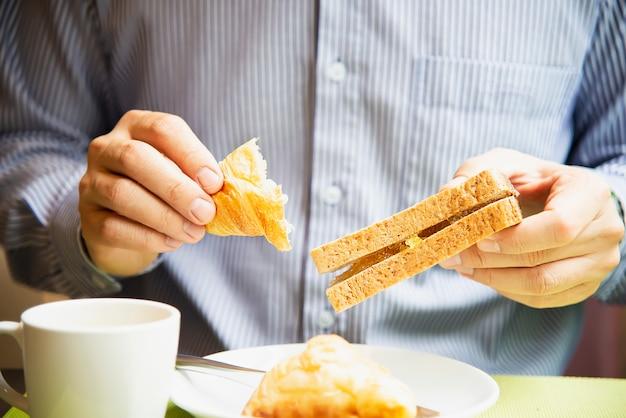 Geschäftsmann essen das amerikanische frühstück, das in ein hotel eingestellt wird Kostenlose Fotos