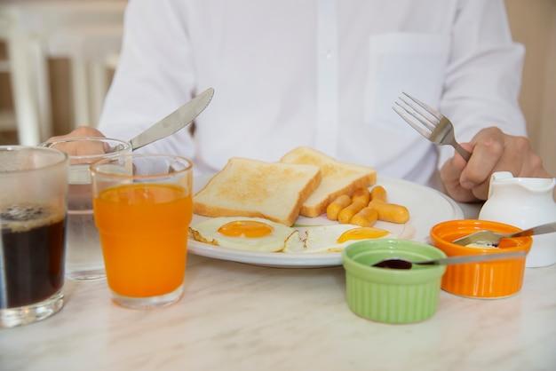 Geschäftsmann essen das amerikanische frühstück, das in einem hotel eingestellt wird Kostenlose Fotos
