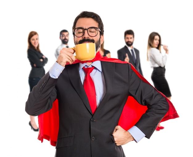 Geschäftsmann gekleidet wie superheld kaffee trinken Premium Fotos