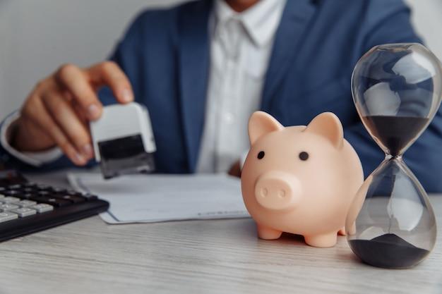 Geschäftsmann genehmigt vertrag im amt. rosa sparschwein mit stapel von münzen und sanduhr auf hölzernem schreibtisch nahaufnahme. zeit ist geldkonzept Premium Fotos