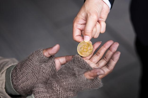 Geschäftsmann gibt seinem obdachlosen sein goldbitcoin Premium Fotos