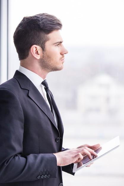 Geschäftsmann hält eine tablette im büro. Premium Fotos