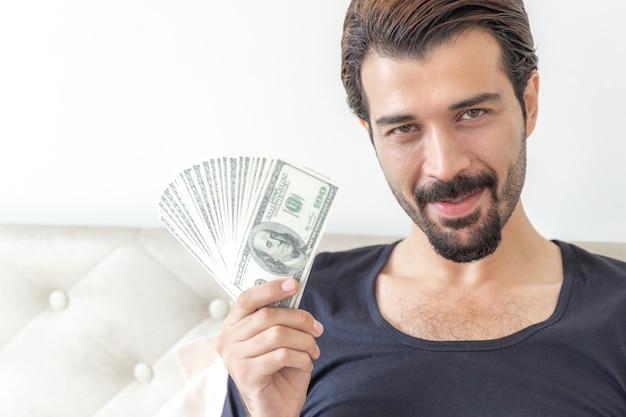 Geschäftsmann hält geld us-dollar-scheine im home office Kostenlose Fotos