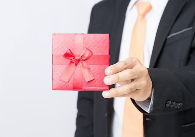 Geschäftsmann hält heraus den geschenkrotkasten Premium Fotos