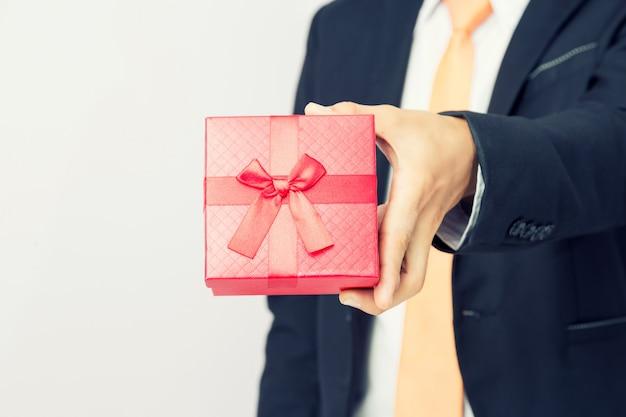 Geschäftsmann hält heraus den roten kasten des geschenks, lokalisierten hintergrund Premium Fotos