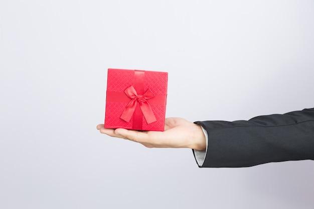 Geschäftsmann hält heraus den roten kasten des geschenks Premium Fotos