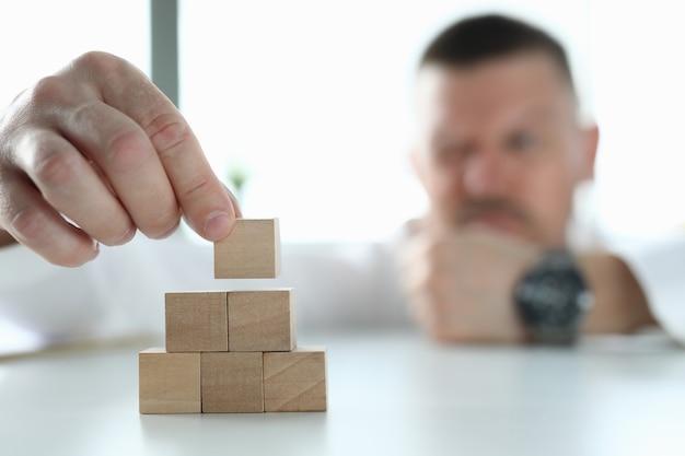 Geschäftsmann hält holzwürfel in den händen und baut pyramide. Premium Fotos