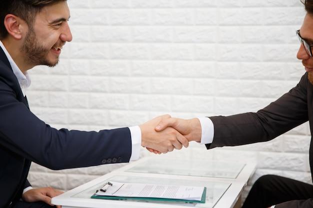 Geschäftsmann händeschütteln, um einen deal mit seinem partner zu besiegeln Premium Fotos