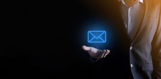 Geschäftsmann hand hält e-mail-symbol, kontaktieren sie uns per newsletter e-mail und schützen sie ihre persönlichen daten Premium Fotos