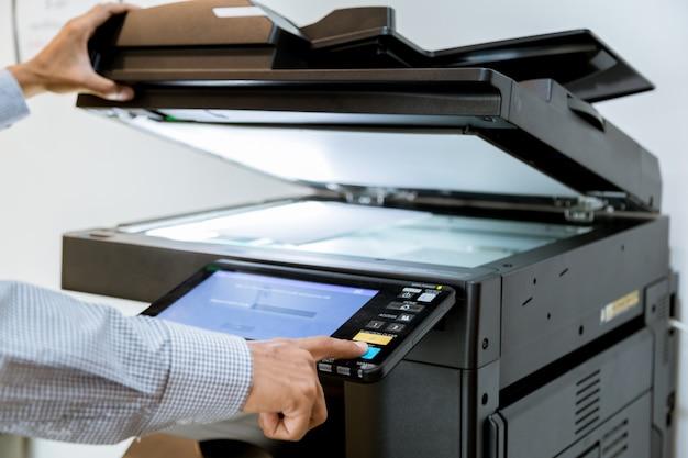 Geschäftsmann handpresseknopf auf panel des druckers Premium Fotos