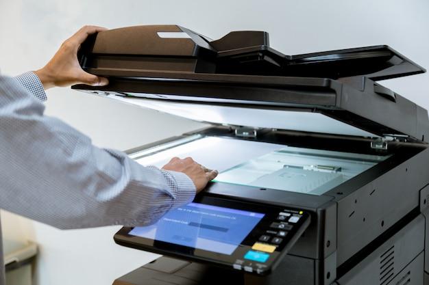 Geschäftsmann handpresseknopf auf platte des druckers, druckerscanner-laser-bürokopie-maschinenversorgungen beginnen Premium Fotos